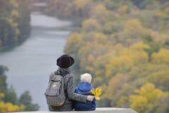 Matka i syn siedzimy na wyższości Jesień Rzeka i f obraz royalty free