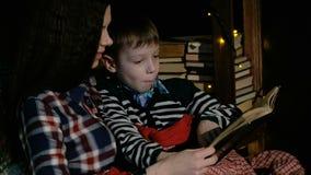 Matka i syn siedzimy w krześle i czytanie książka zawijał w koc zbiory