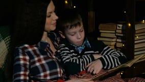 Matka i syn siedzimy w krześle i czytanie książka zawijał w koc zdjęcie wideo