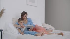 Matka i syn używa cyfrową pastylkę w sypialni w domu Frontowy widok szczęśliwy caucasian syna i matki używać cyfrowy zbiory