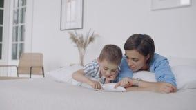 Matka i syn używa cyfrową pastylkę w sypialni w domu Frontowy widok szczęśliwy Kaukaski matki i syna używać cyfrowy zbiory