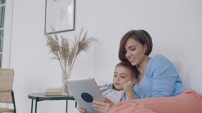 Matka i syn używa cyfrową pastylkę w sypialni w domu Frontowy widok szczęśliwy Kaukaski matki i syna używać cyfrowy zdjęcie wideo
