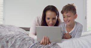 Matka i syn używa cyfrową pastylkę w sypialni 4k w domu zbiory