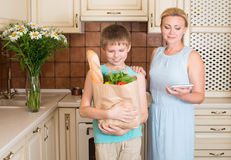 Matka i syn w kuchni z papierowym torba na zakupy pełno ve Obraz Royalty Free