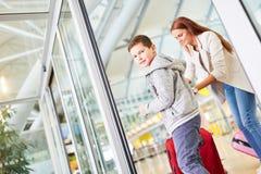 Matka i syn z bagażem w lotniskowy śmiertelnie zdjęcie stock