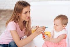 Matka karmi nowonarodzonego dziecka w domu z puree fotografia stock