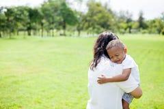 Matka mieszana amerykanin afrykańskiego pochodzenia chłopiec niesie jej dzieciaka w parku Fotografia Royalty Free