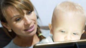 Matka ogląda jej syna który używa laptop zbiory