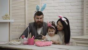 Matka, ojciec i córka, malujemy Easter jajka Szczęśliwa rodzina przygotowywa dla wielkanocy Śliczna małe dziecko dziewczyna zbiory wideo