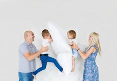 Matka, ojciec i dwa dziecka ma poduszki walkę w sypialni, w domu zdjęcie royalty free