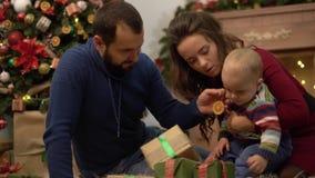 Matka, ojciec i mały dziecka obsiadanie na podłodze w pokoju z boże narodzenie dekoracją, Mężczyzna daje małemu teraźniejszości p zbiory wideo