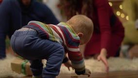Matka, ojciec i mały dziecka obsiadanie na podłodze w pokoju z boże narodzenie dekoracją, Małe dziecko próbuje chodzić zbiory