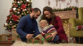 Matka, ojciec i mały dziecka obsiadanie na podłodze w pokoju z Bożenarodzeniową dekoracją, Dziecko bawić się z teraźniejszością zbiory wideo