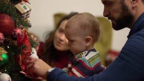 Matka, ojciec i mały dziecko siedzi blisko dekorującej choinki w górę, Obsługuje mienia dziecka blisko jedlinowego drzewa, seans zbiory wideo