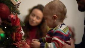 Matka, ojciec i mały dziecko siedzi blisko dekorującej choinki zamkniętej w górę, Obsługuje mienia dziecka blisko jedlinowego drz zdjęcie wideo