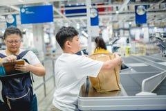 Matka płacił przy kontuarem wynagrodzenie w centrum handlowym z synem trzyma sukienną torbę obraz stock
