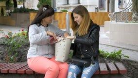 Matka pokazuje jego dorosłej córce jego torby obsiadanie na ławce w mieście Kobiety pokazują ich emocje po robić zakupy zdjęcie wideo
