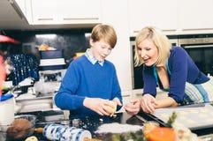 Matka pomaga jej syna robi ciastkom Zdjęcie Stock