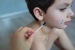 Matka rysuje zieleni punkty na skórze Fotografia Royalty Free