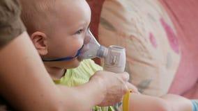 Matka trzyma maskę na dziecko inhalatorze i oddycha medycynę w domu Taktuje rozognienie drogi oddechowe przez zbiory wideo