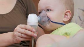 Matka trzyma maskę na dziecko inhalatorze i oddycha medycynę w domu Taktuje rozognienie drogi oddechowe przez zbiory