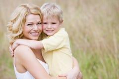 matka trzymać na zewnątrz uśmiechniętego syna Obraz Stock