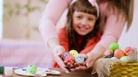Matka trzyma ręki córki w których Wielkanocni jajka zbiory