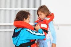 Matka ubiera córki w kamizelce ratunkowej obraz stock