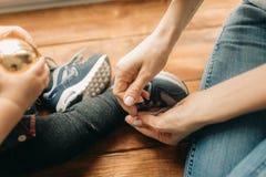 Matka wiąże shoelaces jej małe dziecko obrazy royalty free