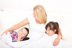 Matka z córką i synem relaksuje w łóżku obraz stock