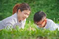 Matka z córką w parku, Macierzysty nauczanie syn pisze na notatniku i siedzącym pinkinie w parku zdjęcia royalty free
