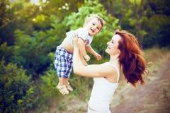 Matka z długim kędzierzawym czerwonym włosy bawić się z jej synem w parku Zdjęcia Royalty Free