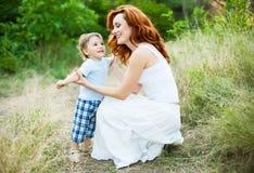 Matka z długim kędzierzawym czerwonym włosy bawić się z jej synem w parku obraz royalty free