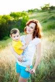 Matka z długim kędzierzawym czerwonym włosy bawić się z jej synem w parku fotografia royalty free