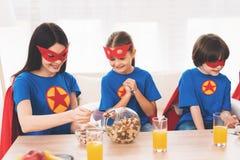Matka z dziećmi w czerwonych i błękitnych kostiumach bohaterzy One w maskach w deszczowach i obrazy royalty free