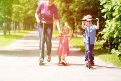 Matka z dzieciakami jedzie hulajnoga w lecie Obrazy Stock
