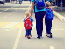 Matka z dzieciakami jedzie wzdłuż drogi na hulajnoga Zdjęcia Royalty Free
