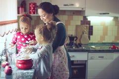 Matka z dzieciakami przy kuchnią Obraz Royalty Free