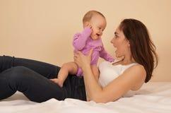 Matka z dzieckiem bawić się w łóżku Zdjęcie Royalty Free