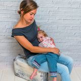 Matka z dzieckiem blisko walizki przeciw ściana z cegieł gira obraz royalty free