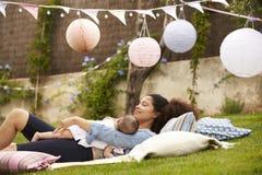 Matka Z dzieckiem Relaksuje Na dywaniku W ogródzie Wpólnie Obrazy Royalty Free