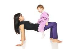 Matka z dzieckiem robi ćwiczeniom nad bielem Fotografia Stock