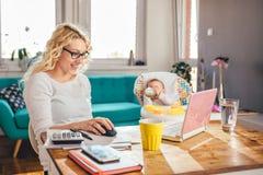 Matka z dzieckiem używa laptopu biuro w domu Obrazy Royalty Free