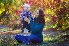 Matka z dzieckiem w parku siedzi pod drzewem Fotografia Royalty Free