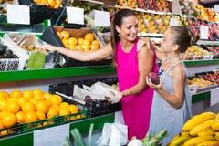 Matka z dziewczyną podnosi różne owoc Zdjęcie Royalty Free