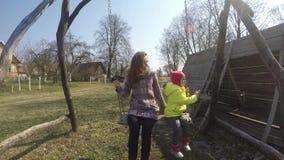 Matka z dziewczyny dziecka chlaniem na retro drewnianej huśtawce w wczesnej wiośnie zbiory wideo