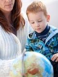 Matka z imbirową chłopiec studiowania kulą ziemską w domu Obrazy Stock