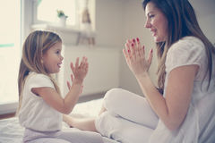Matka z jej ślicznym małym córki obsiadaniem na łóżku Obrazy Royalty Free