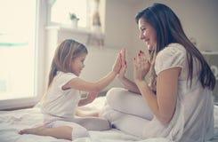 Matka z jej ślicznym małym córki obsiadaniem na łóżku Obrazy Stock