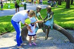 Matka z jej córką blisko matallic rzeźby w parku Zdjęcie Stock